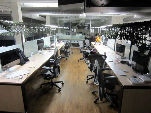 Two rows of empty desks in the centre aisle of Shopify's main office