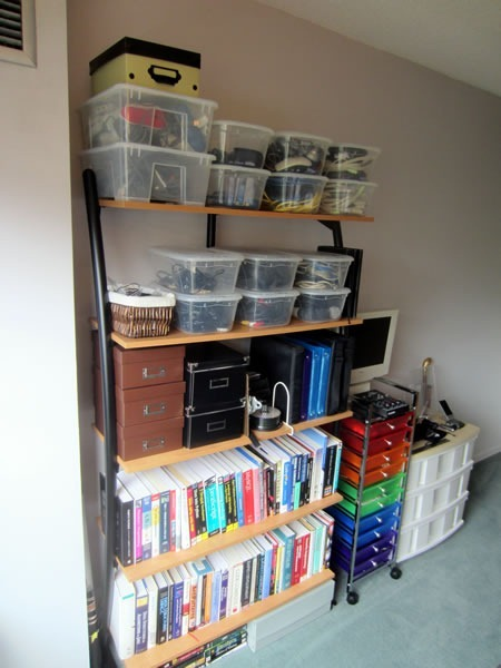Bookshelves packed with books, plus photo boxes of files and many plastic bins full of wiring and other tech equipment