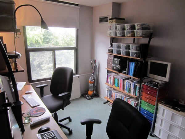 Joey's home office as seen from the desks, showing a windows overlooking treetops and the bookshelves and organizers