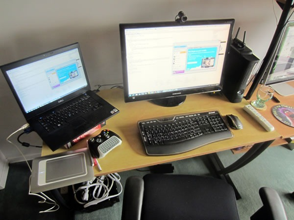 "The left side of Joey's workstation, with a Dell 15"" laptop, 25"" Samsung monitor, Wacom drawing tablet, Xbox and wireless controller and office chair"