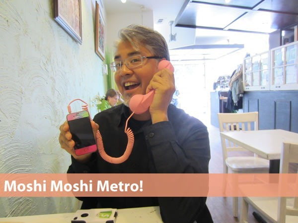 """Moshi Moshi Metro!"" Joey deVilla at Cafe Novo, holding Verna Kulish's pink iPhone connected to a pink Moshi Moshi handset."