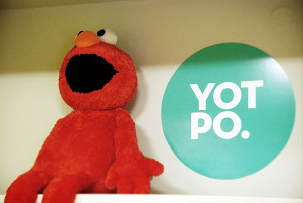 An Elmo doll sitting beside the Yotpo logo