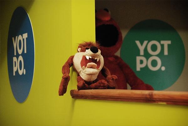 "A ""Tasmanian Devil"" doll, sitting between two Yotpo logos"