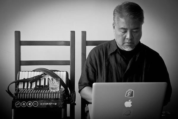 Joey deVilla works on his Macbook Pro, with his accordion and a glass of whiskey by his side.