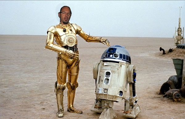 Reg Braithwaite's head on C-3PO's body, standing beside R2-D2 on the Tattooine desert.