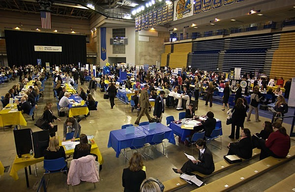A traditional job fair: a gym with stations made of folding tables with prospective employers at each one. It looks like bureaucratic Hell on Earth.