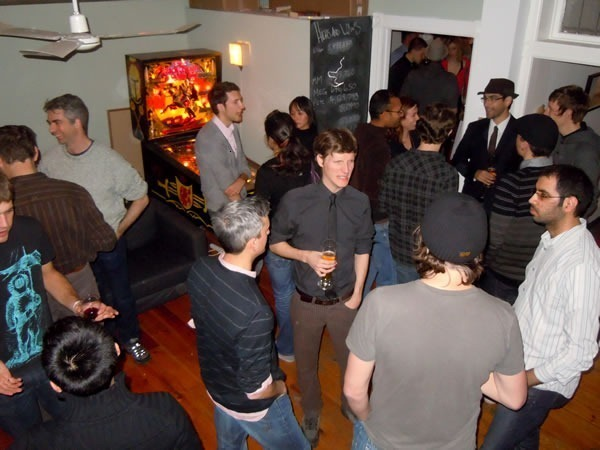 A party crowd in Unspace's back room enjoying their drinks and conversation. A pinball machine is in the background.