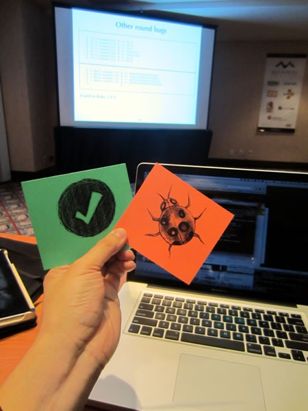 "Joey deVilla holding up ""Feature"" and ""Bug"" cards in front of his laptop."