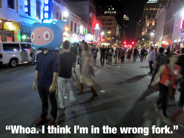Guy wearing a giant Octocat head standing in the middle of Austin's 6th street during South by Southwest