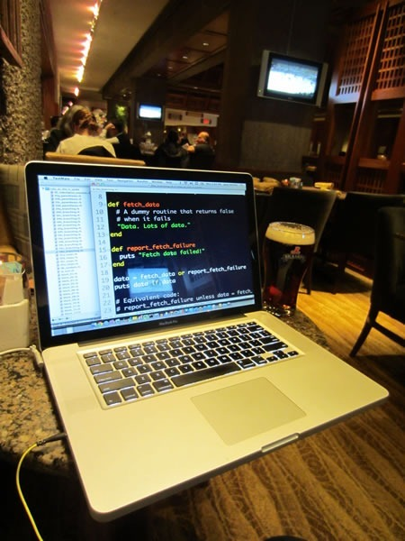 Joey deVilla's MacBook Pro displaying Ruby code. A pint glass of Rickard's Red is beside it.