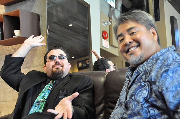 Justin Angel (in a suit) and Joey deVilla (in an Aloha shirt) sitting in a cafe
