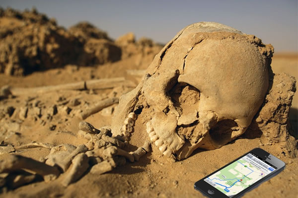 Skeleton in the desert beside an iPhone displaying Apple Maps