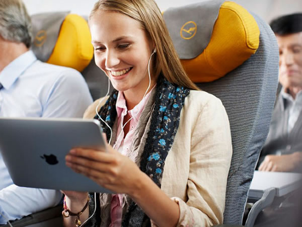 Woman sitting in airplane passenger seat, smiling as she uses an iPad