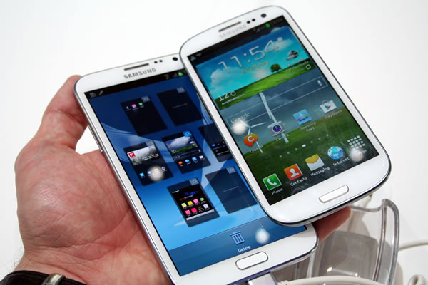 Hand holding both a Samsung Galaxy Note 3 and a Galaxy S4 phone.