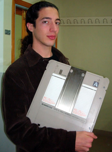Guy holding an optical disk cartridge in his arm like a book