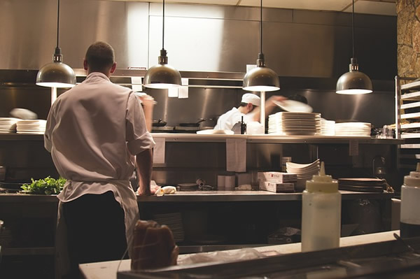 Waiter and cook working in a restaurant.