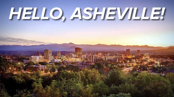 Photo: The city of Asheville, North Carolina in the sunset (or sunrise), with forest in the foreground and mountains in the background. Heading: HELLO, ASHEVILLE!