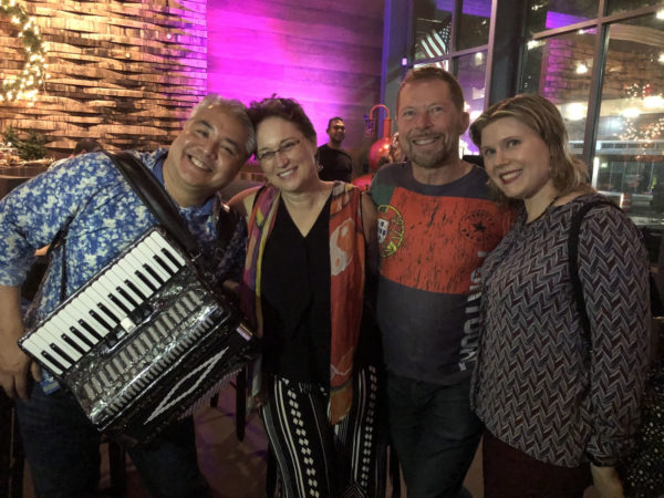 Photo: From left to right, Joey deVilla (with accordion), Lyssa Adkins, Alistair Cockburn, and Anitra Pavka smile at an Agile Social party at Copper Shaker, St. Petersburg, Florida, December 17, 2018.