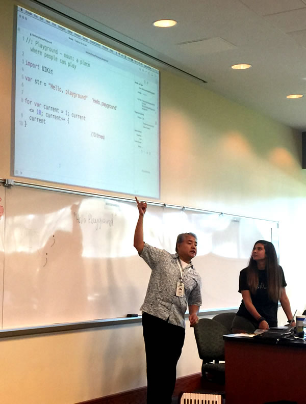 Photo: Joey deVilla points at a projected screen of code with co-presented Angela Don.