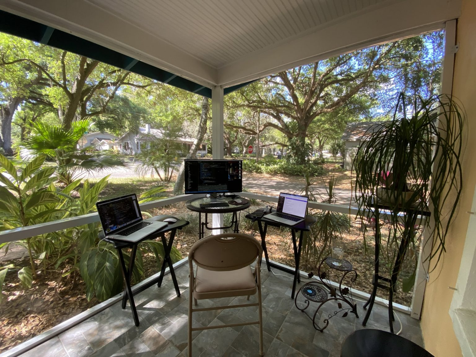 A screened-in front porch with a chair, table, and two laptop computers. There is a view of a garden with a tree-lined residential street corner.