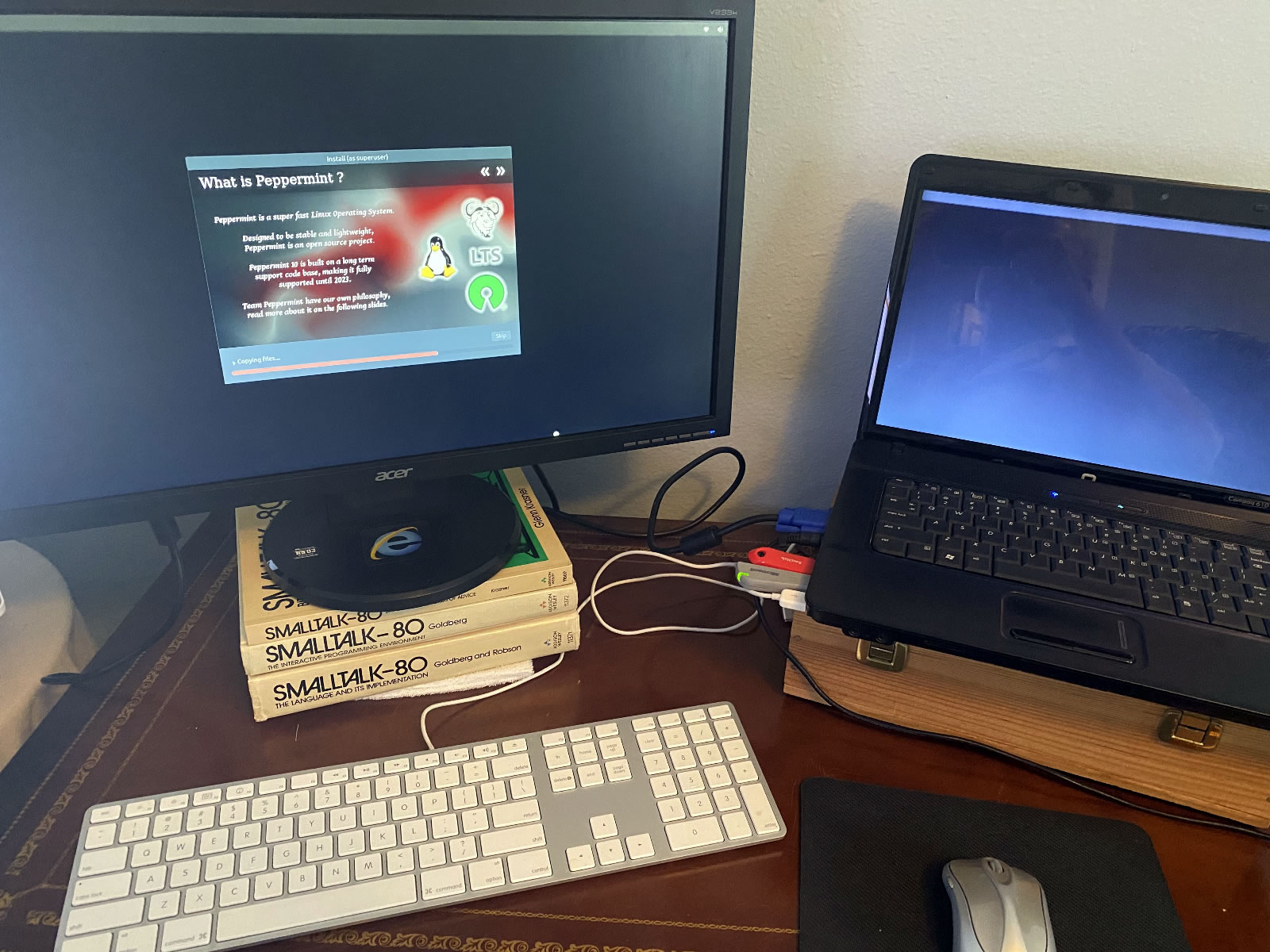 Desk with a Compaq 610 laptop on a wooden box, Acer VGA monitor on a stack of Smalltalk-80 books, an Apple wired keyboard and a Microsoft mouse.