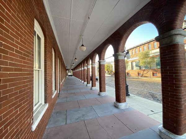 Photo: A long shot of the sidewalk in front of The Undercroft. The Undercroft is a red brick building with white windows, and the walkway is a covered one with brick arches.