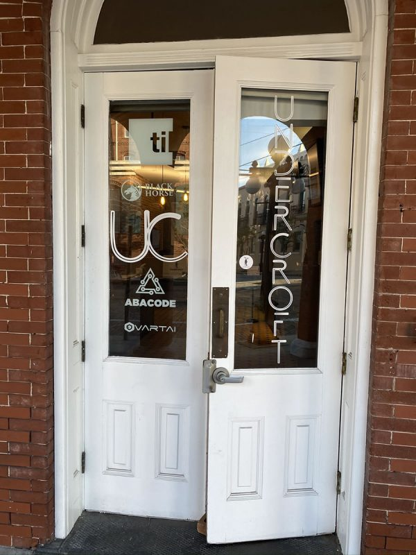 Photo: The front door of The Undercroft. Two white wooden double doors in an arched doorway. The Windows on the doors bear the logos of The Undercroft, til, Black Horse, UC, Abacode, and Vartai.