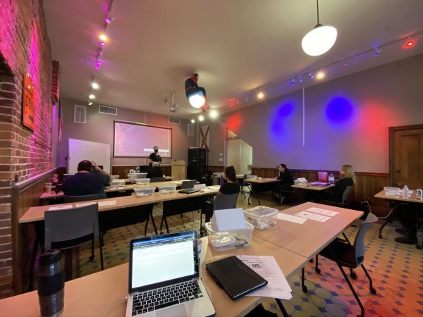 Photo: The Undercroft's classroom. A room with an exposed brick wall on one side, many large table-sized wooden desks, red, white and blue spotlights and a large projection screen at the front. A Spider-Man mannequin sits atop one of the ceiling lights. A MacBook Pro is in the foreground.