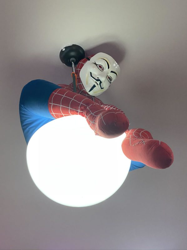 Photo: Close-up shot of the ceiling light in the center of The Undercroft's classroom, which has a Spider-Man mannequin perched atop it. The mannequin is wearing a Guy Fawkes mask.