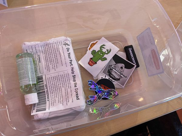 Photo: A shoebox-sized clear plastic tub holding a small bottle of hand sanitizer, a package of surgical masks, assorted stickers, and an Undercroft-branded USB key.