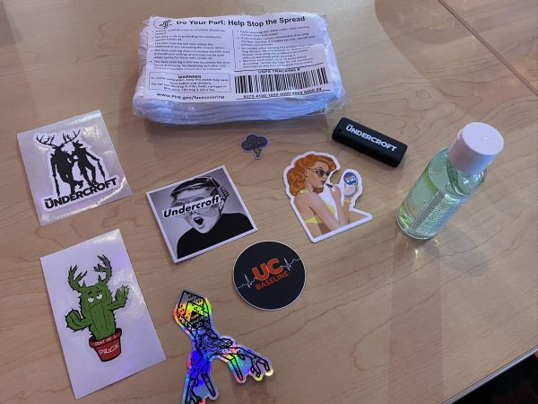 Photo: An assortment of Undercroft and security-related stickers, a packet of surgical masks, a small bottle of hand sanitizer, and an Undercroft-branded USB key.
