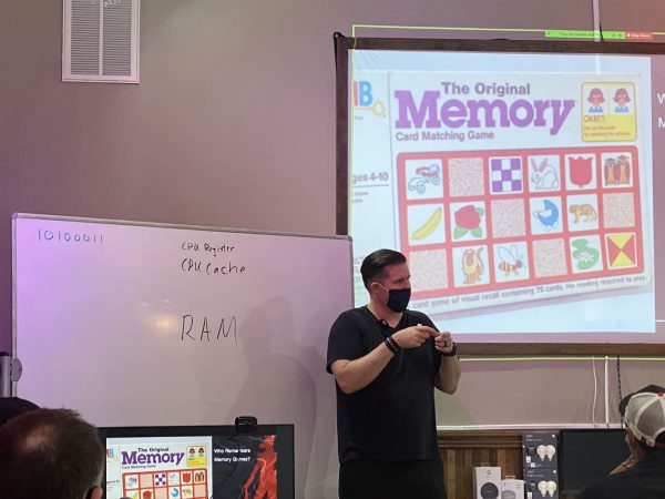 "Photo: The instructor, Tremere, delivers a presentation. Behind him to the left as a whiteboard with ""10100011"", ""CPU register"", ""CPU cache"", and ""RAM"" written on it. Behind and above him to the right is the projection screen, with a photo of the old board game ""Memory"" on display."