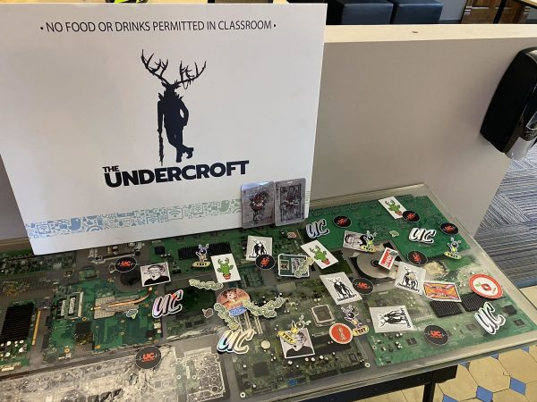Photo: The swag table in The Undercroft's lobby, which has a number of printed circuit boards embedded in it. The table has an assortment of Undercroft and security stickers on it, and at the back in a sign bearing The Undercroft's name and mascot.