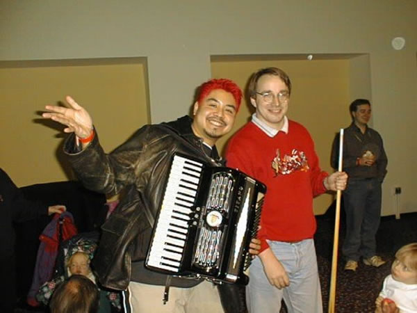 Photo: Joey deVilla, with his accordion, poses with Linus Torvalds, who is holding a pool cue.