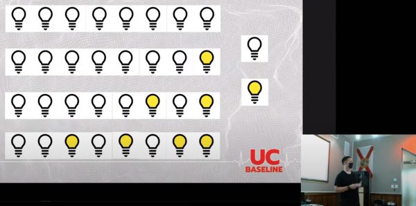 Photo: A slide showing 4 rows of 8 lightbulbs displaying different binary values. Inset in the lower right corner: UC Baseline instructor Tremere lecturing.