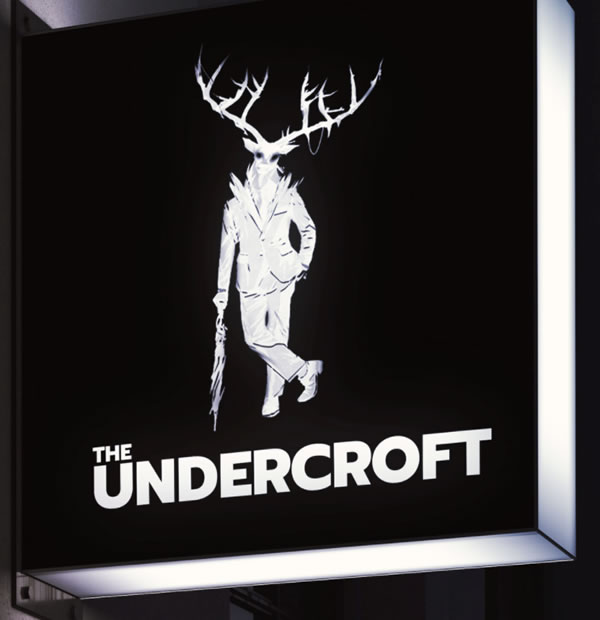 "Photo: The Undercroft sign, featuring the Undercroft's ""mascot"" — a stag standing upright in a suit, leaning jauntily against an umbrella, walking stick-style."