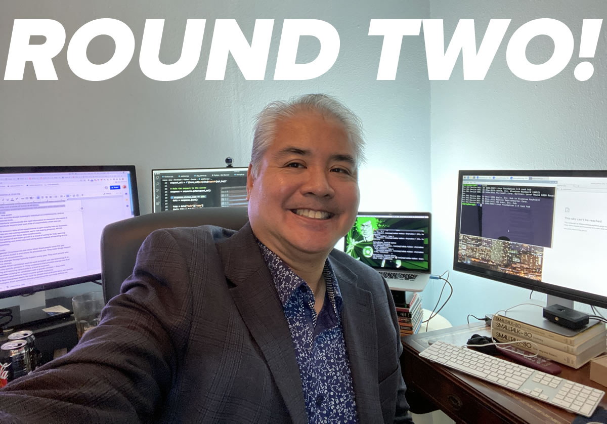"Photo: ""Round Two!"" — Another ""Selfie"" featuring Joey deVilla in a sport jacket and dress shirt sitting at his desks in his home office, with MacBook Pro and three monitors in the background."