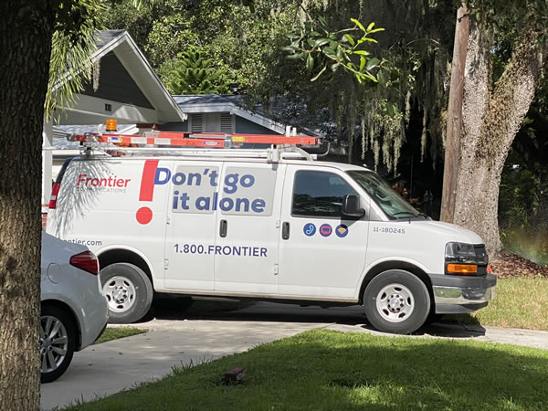 Photo: A van for Frontier, parked in a residential driveway.