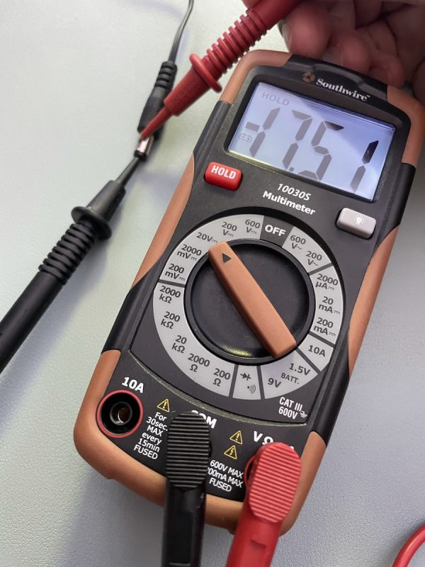 Multimeter being used to measure voltage coming from adapter, with the display showing a negative voltage.