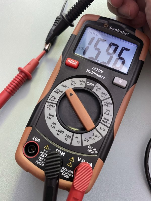 Multimeter being used to measure voltage coming from adapter, with the display showing a positive voltage.