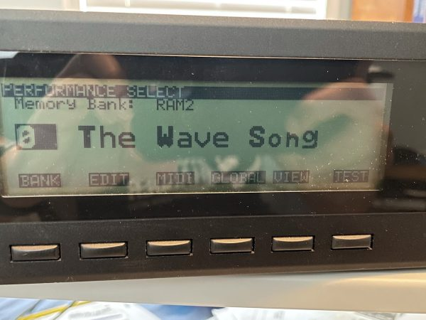 "LCD display of Korg Wavestation A/D displaying the name of the currently selected sound: ""The Wave Song""."