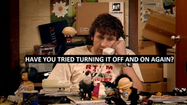 """Still photo from """"The IT Crowd"""" — Rory at his desk on the phone, with the caption """"Have you tried turning it off and on again?"""""""