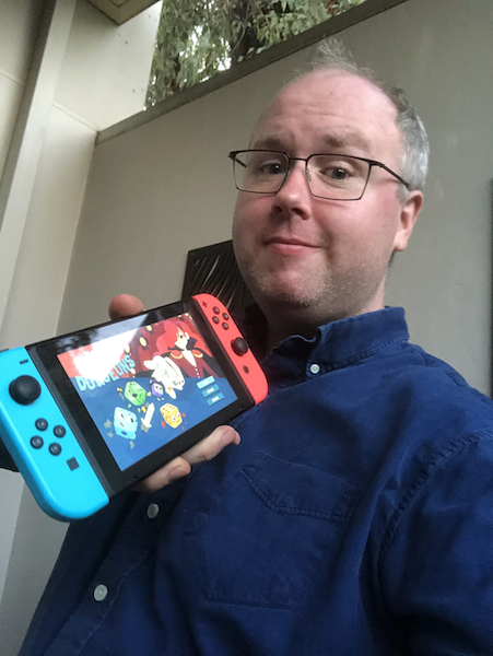 Terry Cavanaugh poses with a Nintendo Switch.